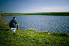 Pesca del hombre en la orilla del lago Foto de archivo