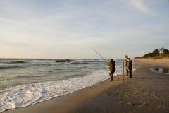 Pesca del hombre en la playa imagenes de archivo