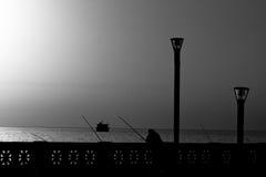 Pesca del hombre en la salida del sol en B/W Imagen de archivo