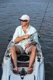 Pesca del hombre en primer del kajak foto de archivo