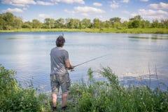Pesca del hombre en un lago Imagen de archivo libre de regalías
