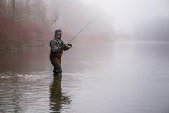Pesca del hombre en un río Foto de archivo