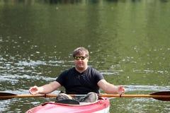 Pesca del hombre joven en el río Fotos de archivo libres de regalías