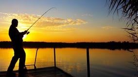 Pesca del hombre joven en un lago en la puesta del sol Imagenes de archivo