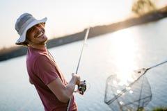 Pesca del hombre joven en un lago en la puesta del sol y la afición del goce Foto de archivo