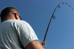 Pesca del hombre joven, pescador que sostiene la barra en la acción Foto de archivo