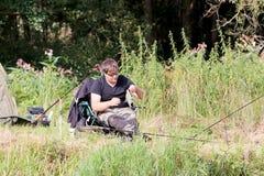 Pesca del hombre joven por el río Foto de archivo libre de regalías