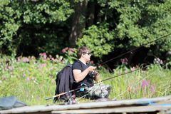 Pesca del hombre joven por el río Imagen de archivo libre de regalías
