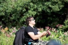 Pesca del hombre joven por el río Fotos de archivo