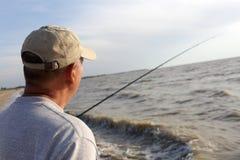 Pesca del hombre mayor en la puesta del sol Imagenes de archivo