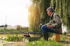 Pesca del hombre mayor en un lago de agua dulce que se sienta pacientemente fotografía de archivo libre de regalías