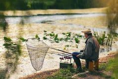 Pesca del hombre mayor en un lago de agua dulce que se sienta pacientemente imagen de archivo libre de regalías