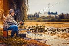 Pesca del hombre mayor en un lago de agua dulce que se sienta pacientemente imagen de archivo