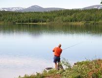 Pesca del hombre por un lago Fotos de archivo libres de regalías