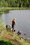 Pesca del hombre por un lago Imagenes de archivo