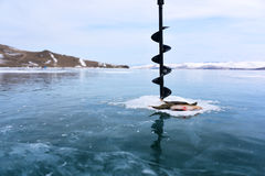Pesca del invierno en el medio del hielo congelado del lago foto de archivo libre de regalías