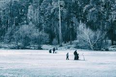 Pesca del invierno Río, lago cerca del bosque en hielo Pescadores, Fishermens durante su tiempo libre preferido Imagen entonada imagen de archivo