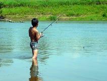 Pesca del muchacho con el giro Imagenes de archivo