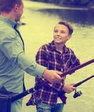 Pesca del muchacho con el hombre en el lago de agua dulce en bosque Fotografía de archivo