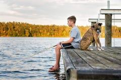 Pesca del muchacho con el perro en muelle en el lago Fotografía de archivo