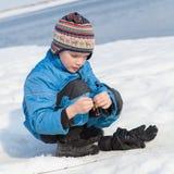 Pesca del muchacho con la barra en el río en invierno Fotos de archivo libres de regalías