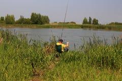 Pesca del muchacho en el lago fotografía de archivo libre de regalías