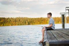 Pesca del muchacho en muelle en el lago Fotos de archivo