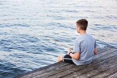 Pesca del muchacho en muelle en el lago Imagen de archivo