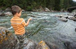 Pesca del niño en el río Imagenes de archivo