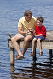 Pesca del padre con il suo figlio su un molo Fotografia Stock