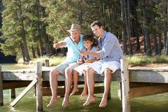Pesca del padre, del figlio e del nipote insieme Immagine Stock
