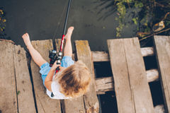 Pesca del pequeño niño del muelle de madera en el lago Fotos de archivo