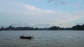 Pesca del pescador del barco en el mar fondo mountian Cat Ba, Vietnam metrajes