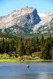 Pesca del pescador de la mosca en el lago en Rocky Mountain National Park Imagen de archivo libre de regalías