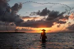 Pesca del pescador del Balinese en una playa en la salida del sol Foto de archivo libre de regalías