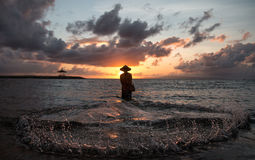 Pesca del pescador del Balinese en una playa en la salida del sol Imagen de archivo