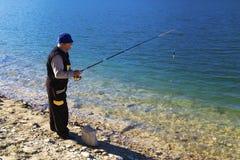 Pesca del pescador en el lago azul Imagenes de archivo