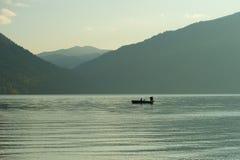 Pesca del pescador en el lago a la mañana brumosa Imagen de archivo