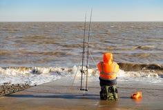 Pesca del pescador en el mar en Penarth en invierno Foto de archivo