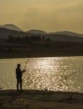 pesca del pescador en la puesta del sol Fotografía de archivo libre de regalías