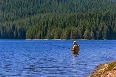Pesca del pescador en un lago Foto de archivo