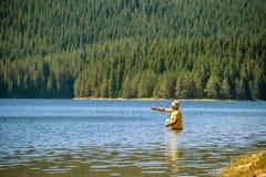 Pesca del pescador en un lago Imagen de archivo