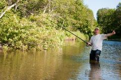 Pesca del pescador en un río Foto de archivo