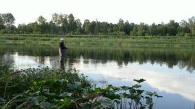 Pesca del pescador en un río tranquilo por la mañana almacen de metraje de vídeo
