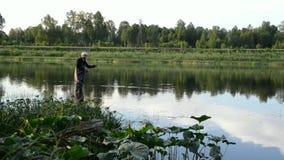 Pesca del pescador en un río tranquilo por la mañana almacen de video
