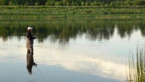 Pesca del pescador en un río tranquilo por la mañana Hombre en las artes de pesca stending en un río metrajes