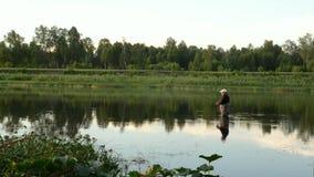 Pesca del pescador en un río tranquilo por la mañana Hombre en las artes de pesca stending en un río y tiros trole almacen de metraje de vídeo