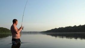 Pesca del pescador en un río tranquilo por la mañana Hombre en las artes de pesca stending en un río y tiros trole metrajes