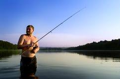 Pesca del pescador en un río tranquilo por la mañana Hombre en las artes de pesca stending en un río y tiros trole Imagen de archivo libre de regalías