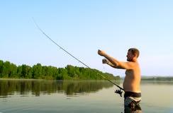 Pesca del pescador en un río tranquilo por la mañana Hombre en las artes de pesca stending en un río y tiros trole Fotos de archivo
